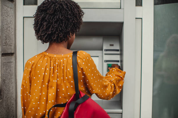 Woman Making A Cash Withdrawal At An ATM stock photo