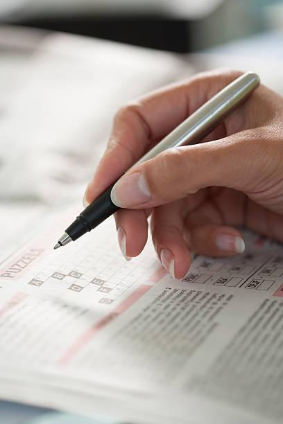 woman making a crossword puzzle with a pen - kreuzworträtsel lexikon stock-fotos und bilder