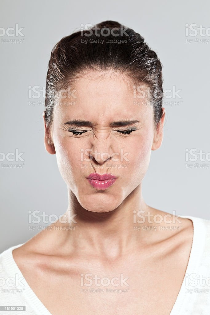 Woman making a face Portrait of  young woman making a face. Studio shot, grey background. 20-24 Years Stock Photo