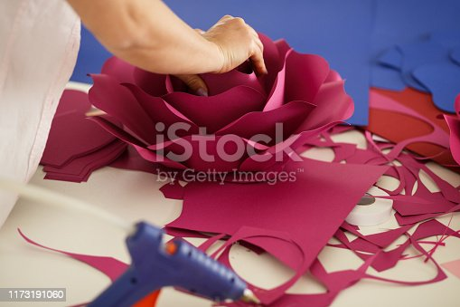 Cut out shot of unrecognizable woman piecing together stencils and flower petals made out of construction paper to craft a beautiful pink paper flower.