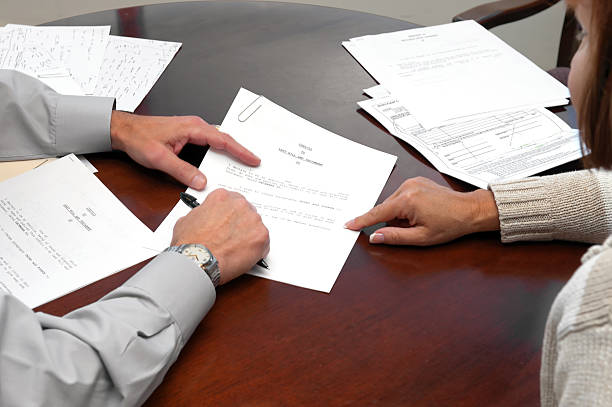 a woman making a formal business agreement signing a will - jodijacobson stock pictures, royalty-free photos & images
