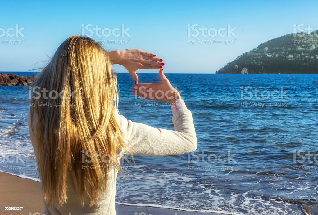 Woman making a frame with her hands at the beach stock photo