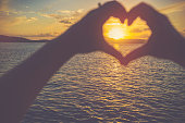 Woman making a heart shape with her hands. It is sunset behind her hands with light reflecting off the ocean. Focus is on the background