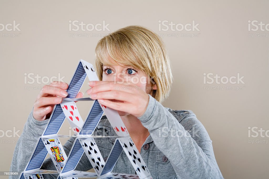 Woman making a house of cards stock photo