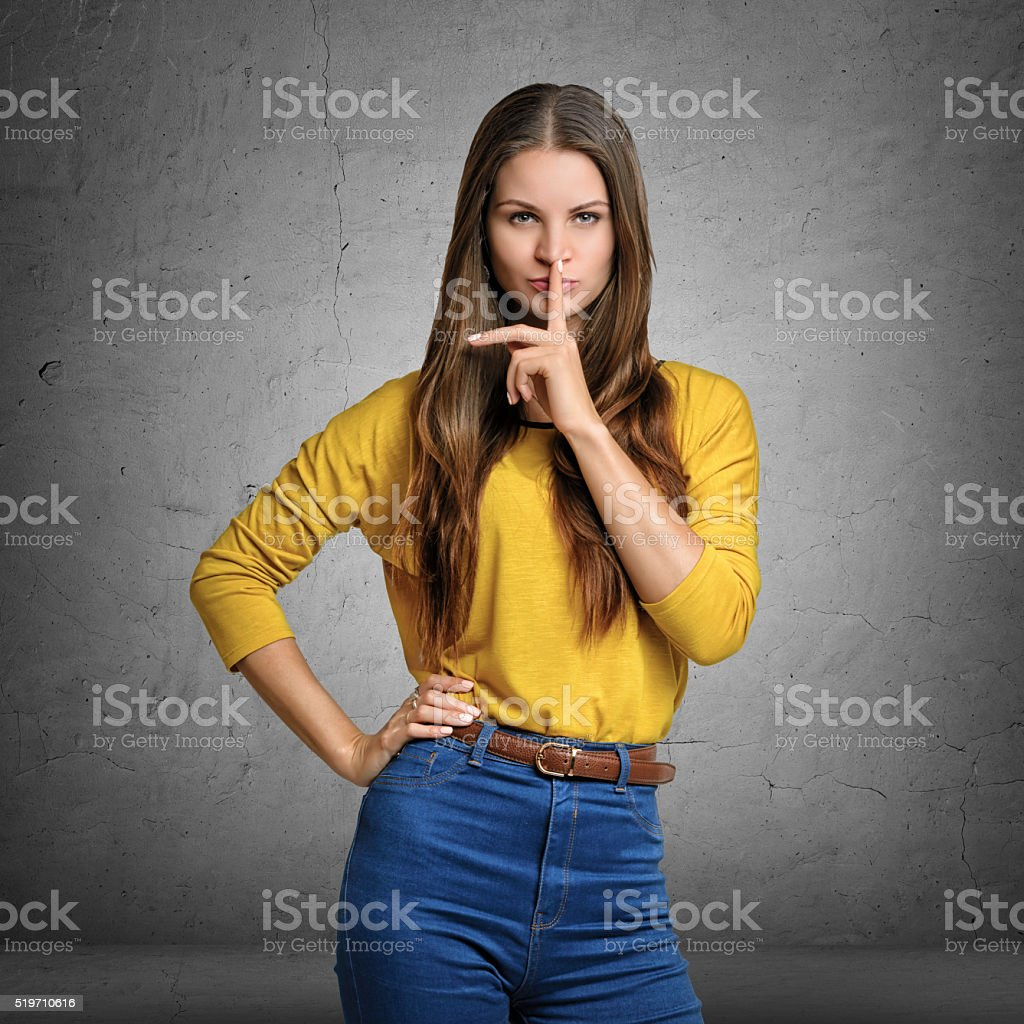 Woman making a hush gesture with her index finger on stock photo