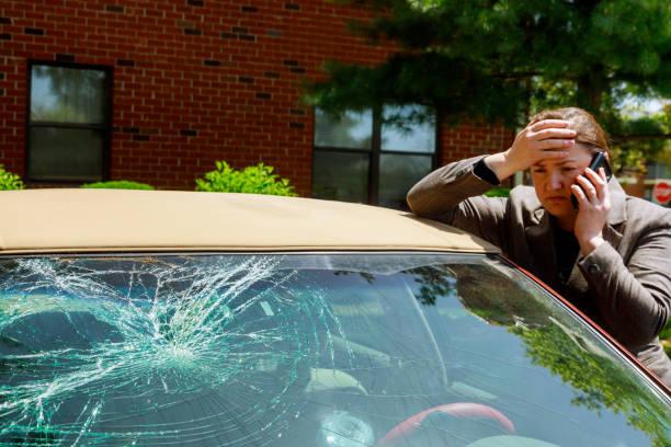 vrouw het maken van een telefoontje naast de beschadigde auto na een auto-ongeluk - voorruit stockfoto's en -beelden