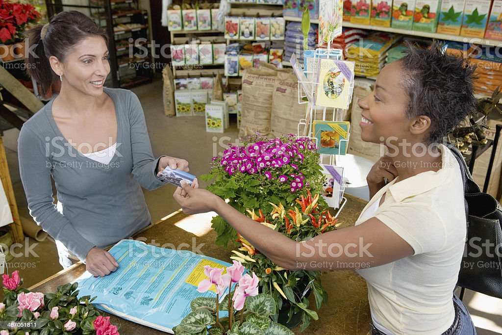 Woman Making a Purchase at Plant Nursery stock photo