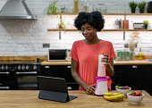 Woman making a smoothie at home following an online recipe
