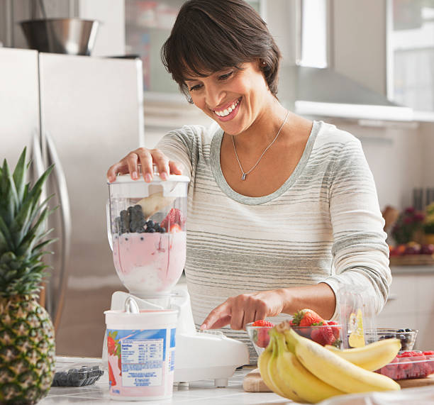 Woman making a smoothie stock photo
