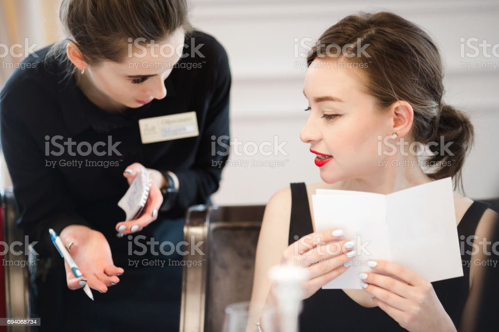 Woman making an order from the waitress menu stock photo