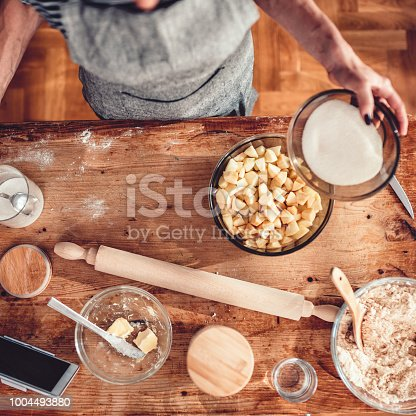 istock Woman making apple pie on wooden table 1004493880