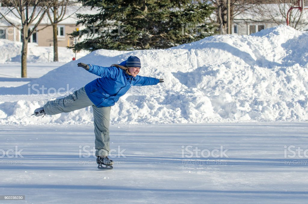 Woman making arabesque while ice skating on an ice rink outdoors stock photo