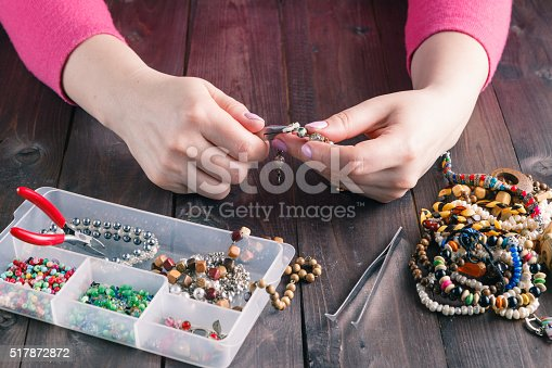 Woman making beaded bracelet with her hands, closeup on wooden table
