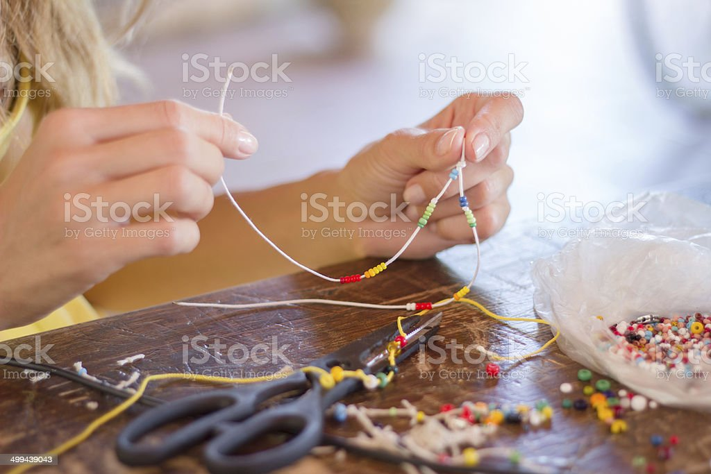 Woman making bracelet of colorful beads stock photo
