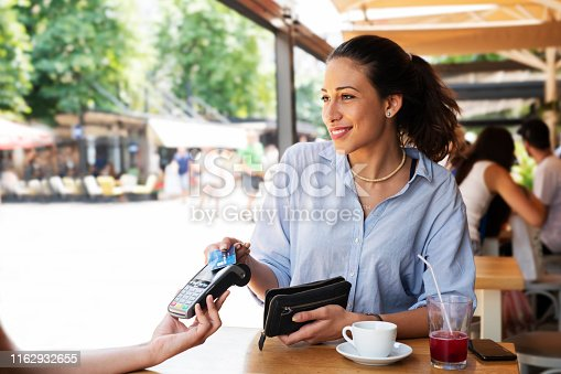 Latino woman making card payment in cafeteria, summer bar.