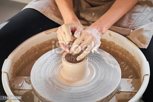 istock Woman making ceramic pottery on wheel, creation of ceramic ware. Concept of women's work, craft 1140287030