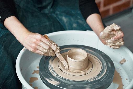 Woman making ceramic pottery on wheel, hands close-up, creation of ceramic ware. Handwork, craft, manual labor, buisness. Earn extra money, turning hobbies into cash and turning passion into job