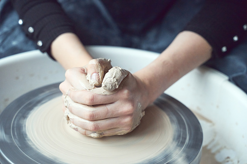 Woman making ceramic pottery on wheel, hands close-up, creation of ceramic ware. Handwork, craft, manual labor, business. Earn extra money, turning hobbies into cash and turning passion into job
