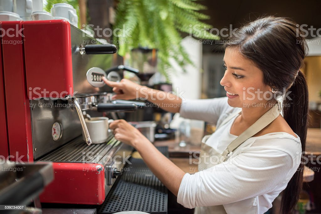 Woman making coffee in a machine royalty-free stock photo