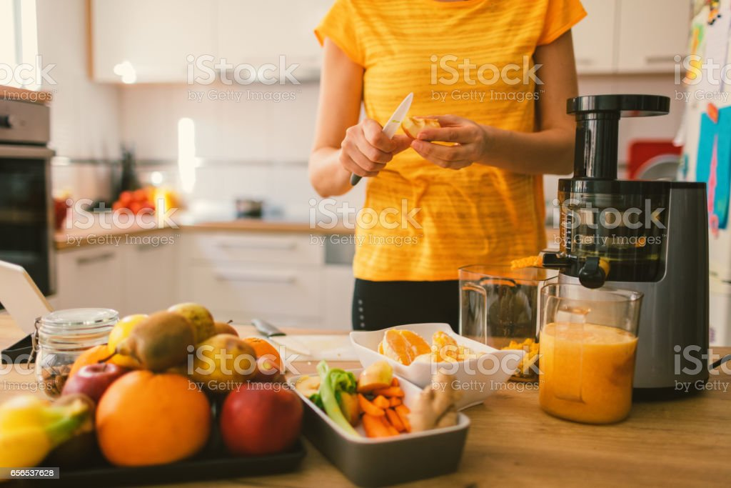 Woman making cold-pressed juice stock photo
