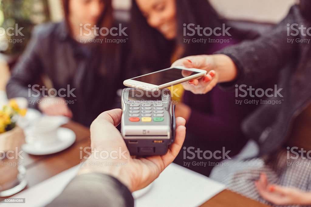 Woman making contactless payment with smartphone bildbanksfoto