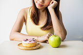 Woman making decision between healthy food and unhealthy food, Healthy and diet lifestyle concept