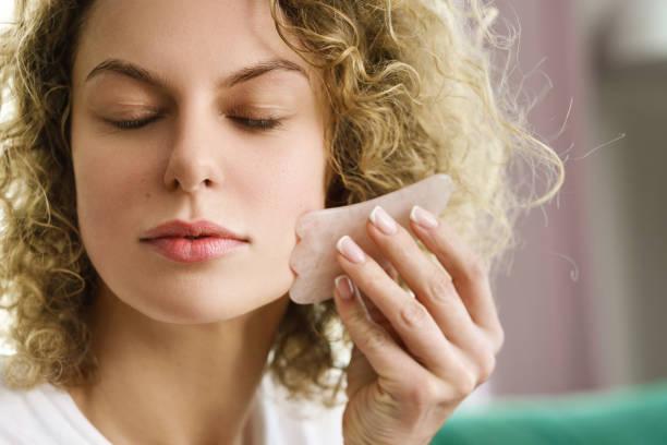 Woman making facial massage with a rose Gua Sha stone stock photo