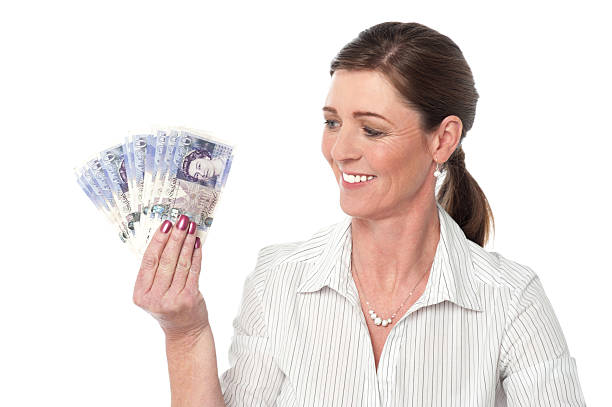 Woman making fan of pound sterling banknotes stock photo