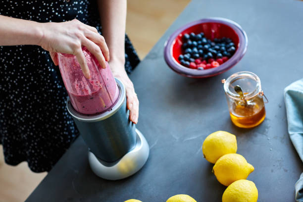 Woman making fruit juice using juicer machine Close up of woman making fruit juice using juicer machine at home in kitchen blender stock pictures, royalty-free photos & images