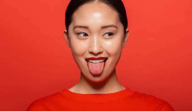 Woman making funny face Close up of young asian woman sticking out tongue and looking away. Korean female model making funny face against red background. sticking out tongue stock pictures, royalty-free photos & images