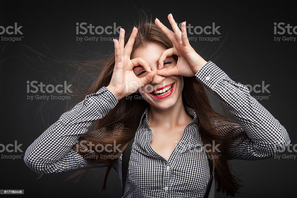 Woman making glasses out of her hands. stock photo