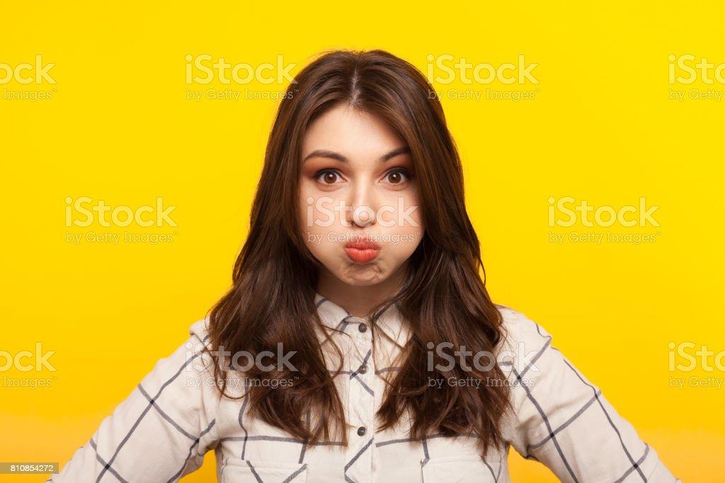 Woman making grimace on yellow stock photo