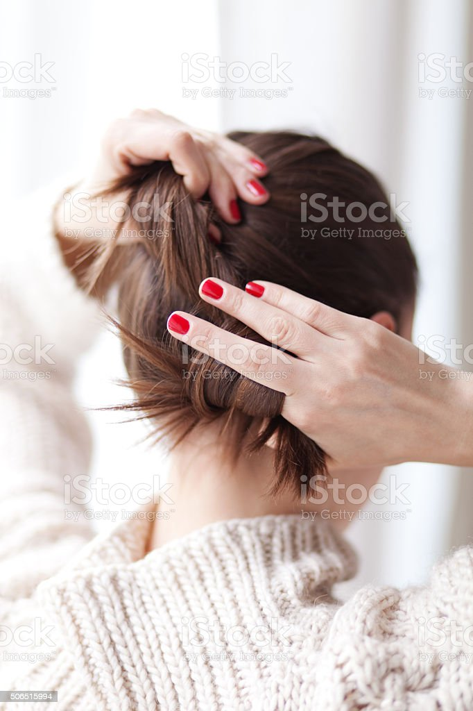 Woman making hair bun stock photo