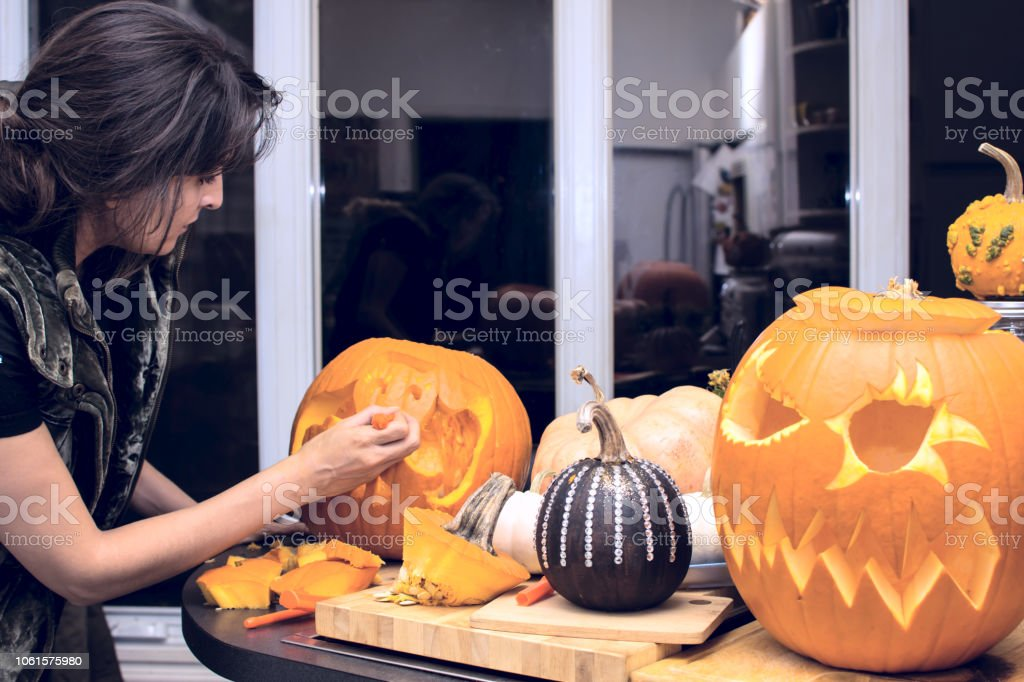 Woman making Halloween pumpkin Jack o'lantern stock photo