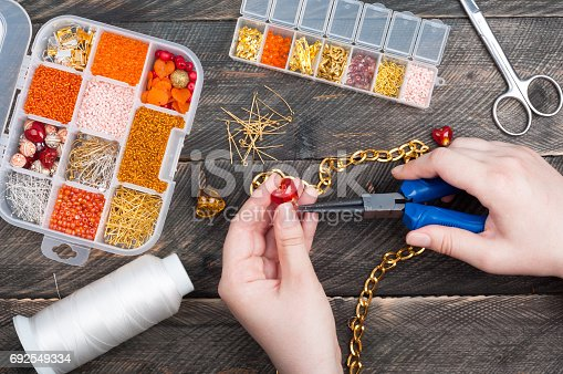 1074436306istockphoto Woman making handmade jewellery. Handmade accessories. Box with beads, glass hearts, accessories for needlework on old wooden background. Top view 692549334