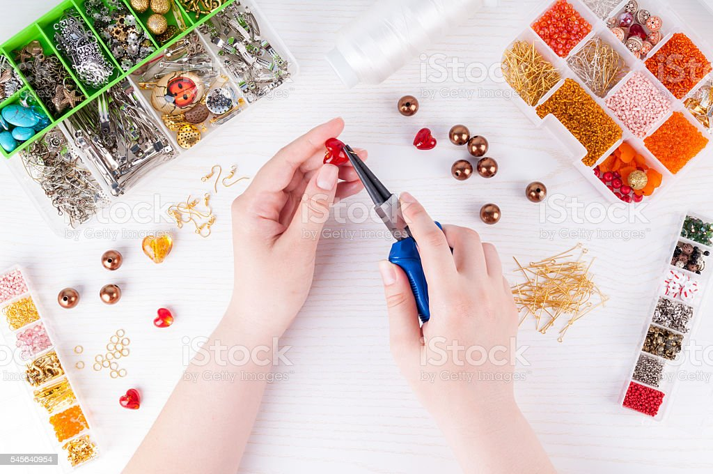 Woman making handmade jewellery. Handmade accessories. Top view stock photo