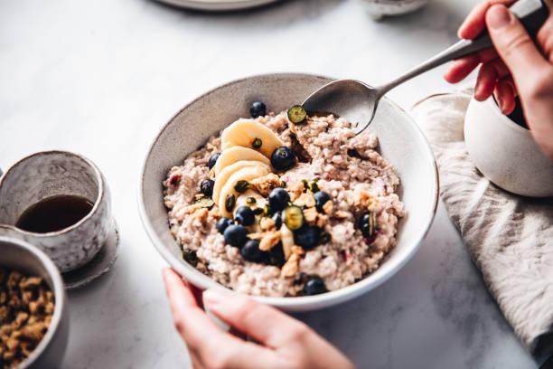 frau macht gesundes frühstück in der küche - frühstück stock-fotos und bilder