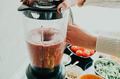 Close-up of woman making smoothie with fruits and vegetables in the kitchen at home