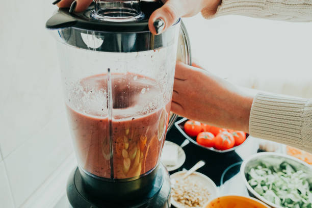 vrouw die gezonde smoothie in de keuken maakt - mixer stockfoto's en -beelden
