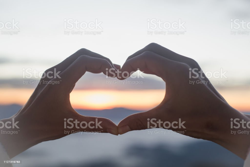 Woman making heart shape during sun rise, God is love concept, Heart...