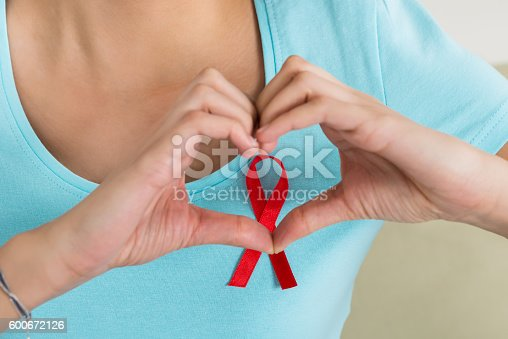 istock Woman Making Heart Shape In Front Of Aids Awareness Ribbon 600672126