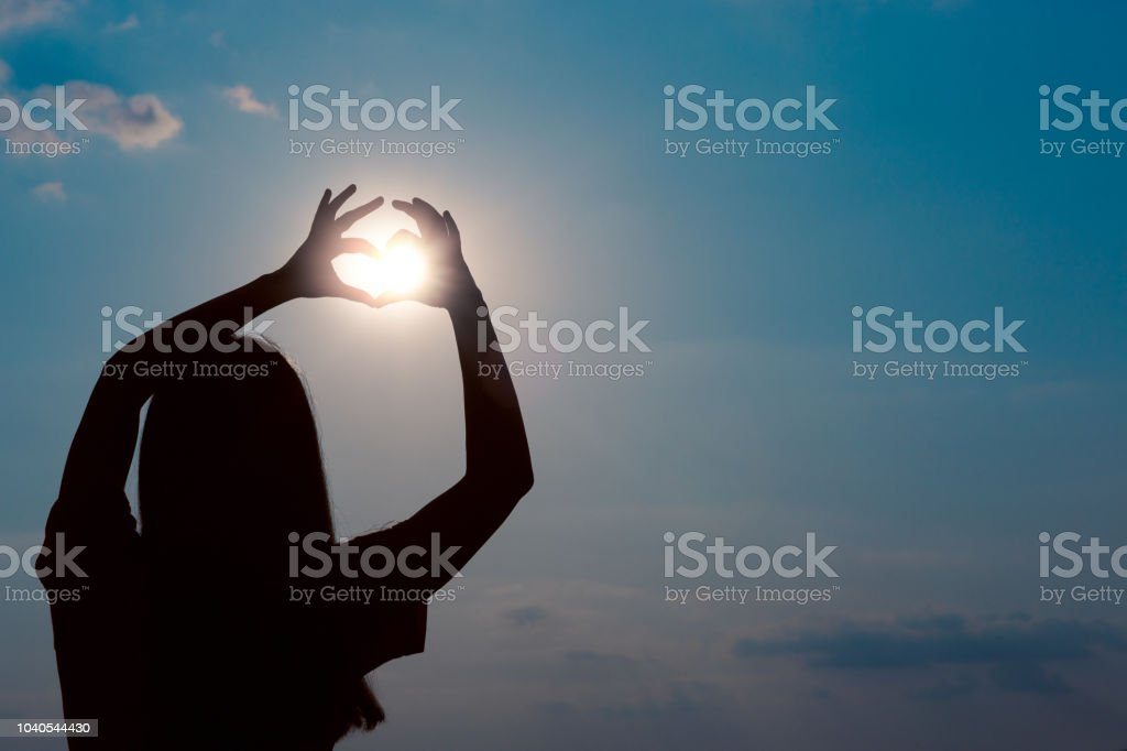 Woman Making Heart Sign Gesture in Sunset Sunlight stock photo