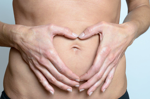 istock woman making heart sign on her belly 496831938