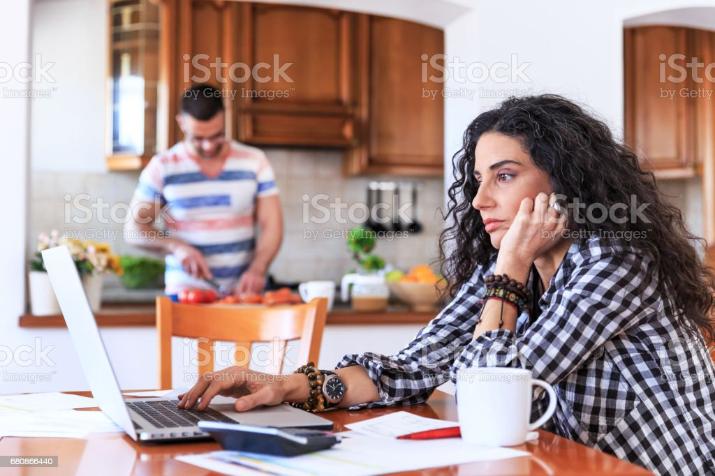 Young woman sitting at home and making home finances. Man behind...