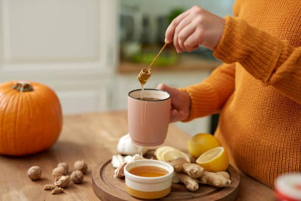 Woman making hot tea with honey stock photo