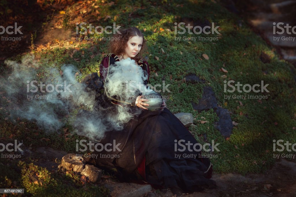 Woman making magical potion. stock photo