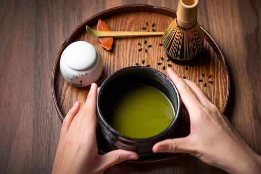 Woman making matcha green tea with traditional accessories for tea ceremony