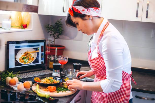 Woman making meal with tutorial – zdjęcie