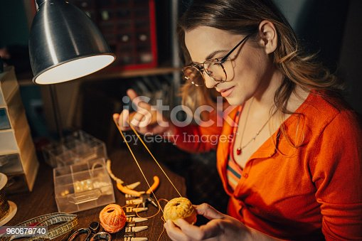 512345816istockphoto Woman making necklace in the workshop 960676740
