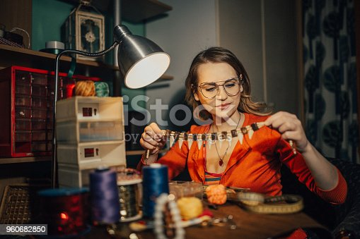 512345816istockphoto Woman making necklace in the workshop 960682850